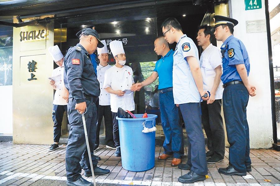7月1日,上海各執法部門聯合進行社區單位垃圾分類專項檢查,指導民眾做好垃圾分類工作。(中新社)