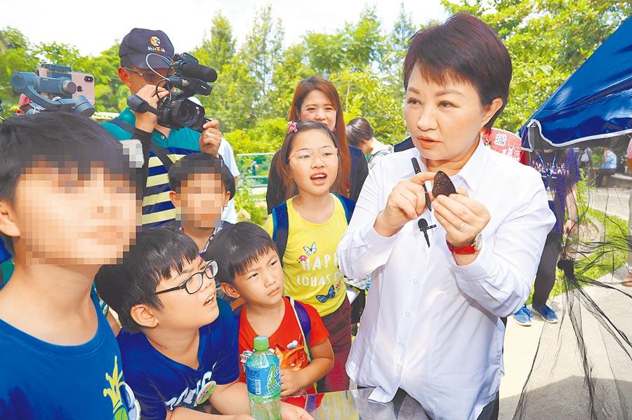 「媽媽市長」盧秀燕(圖右)8日化身紫斑蝶導覽員,告訴小朋友如何記錄飛行路線。(張妍溱攝)