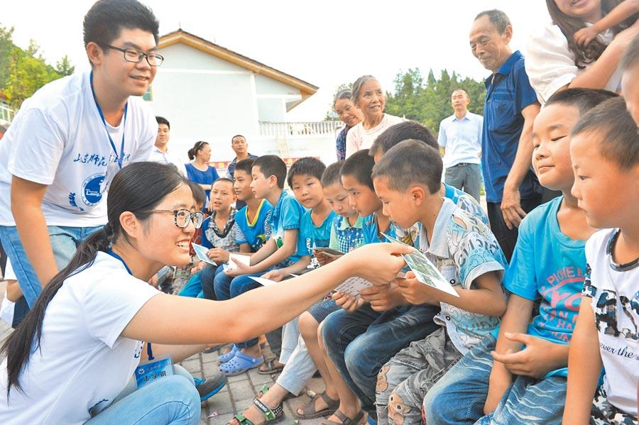 2015年7月23日,大學生志願者到武陵山區扶助留守兒童與空巢老人。(新華社)