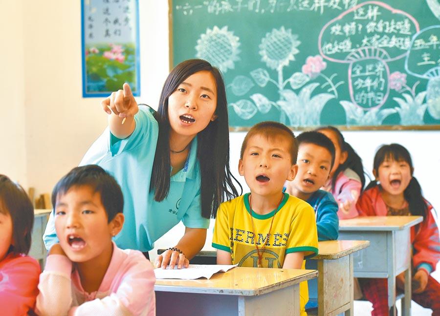 2016年7月17日,山西農大學生熱心扶貧,教導寧武縣懷道完全小學的學生們讀英語單詞。 (新華社)