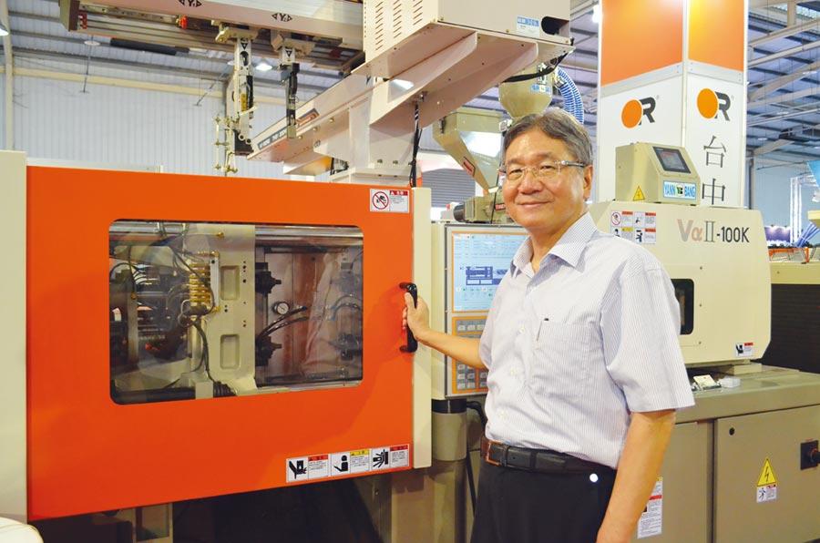 台中精機董事長黃明和與市場當紅的全電式塑膠射出成型機。圖/業者提供