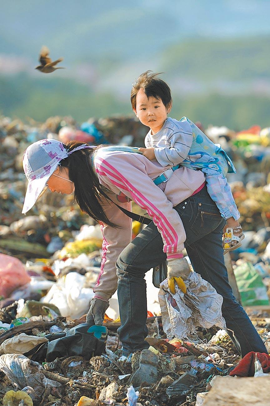 貴陽一位母親背著孩子撿垃圾。(新華社資料照片)