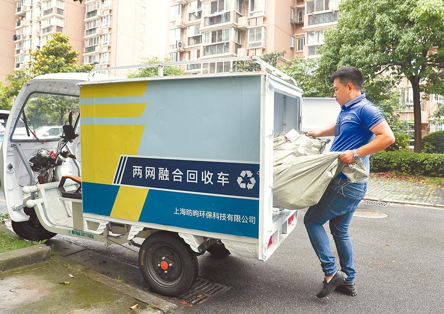 7月1日,上海回收員將在居民家中收集的可回收物裝運上車。(新華社)