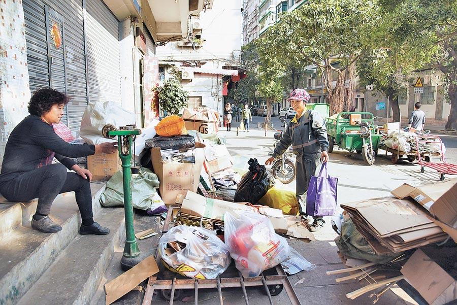 1月29日,廣州環衛工把打掃時撿的紙箱送到廢品收購站賣錢。(新華社)