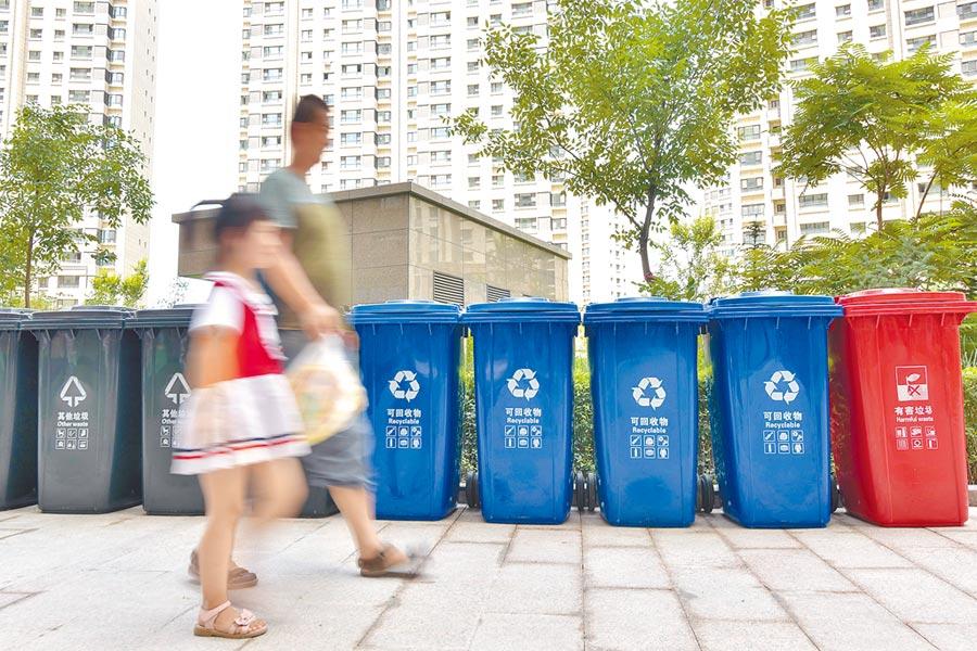 垃圾分類是一場利益重新分配和博弈。圖為烏魯木齊居民7日從垃圾分類桶前經過。(新華社)