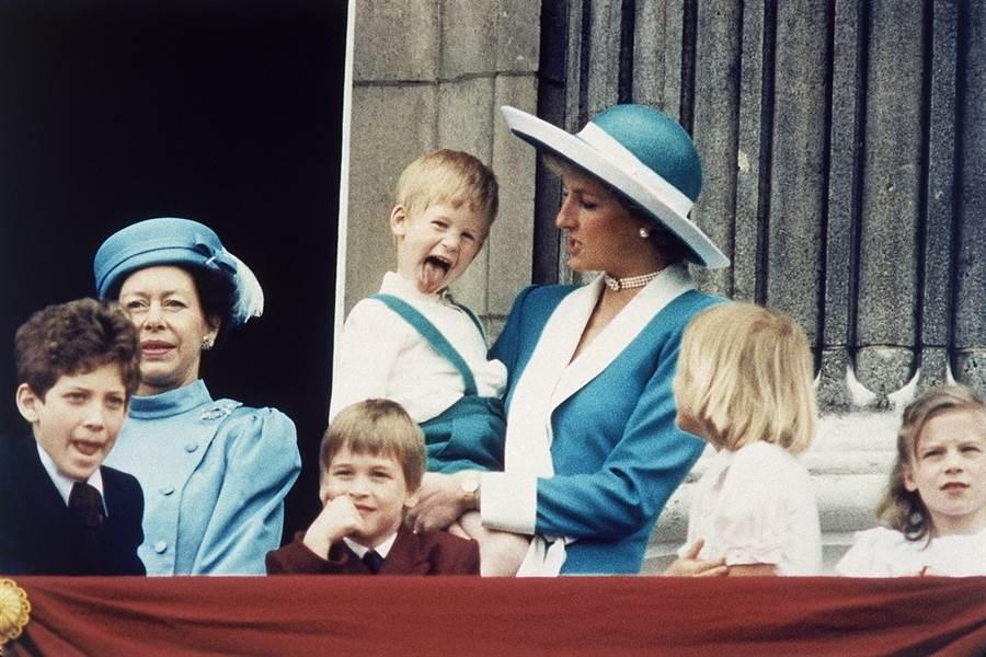 英國媒體報導,哈利王子因王位繼承順位在哥哥威廉之後,從小便不斷被忽略、提醒是「老二」,這點令已故黛安娜王妃相當擔心。圖為1988年王室成員在白金漢宮陽台亮相的畫面,圖中伸長舌頭、由黛妃抱著的小男孩正是哈利王子,前排托腮男孩為威廉王子。(圖/美聯社)