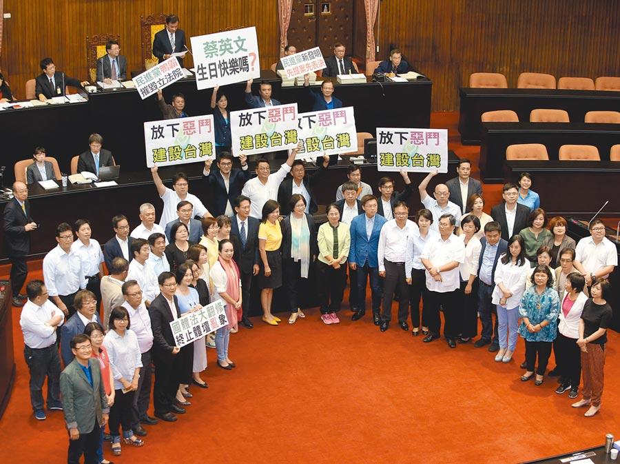 2015年立法院臨時會三讀修正通過《國民體育法》,國民黨團在後方舉牌,表達對強渡前瞻預算的不滿。 (本報資料照片)