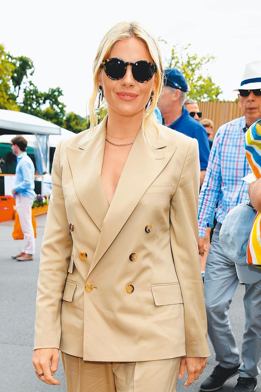 席安娜米勒穿米色Ralph Lauren Collection米色雙排釦西裝看球賽,輕鬆愜意。(CFP)