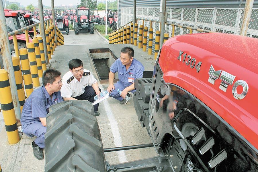 2011年一拖集團收購法國麥考密克公司,更名為一拖法國有限公司。圖為2013年7月26日,海關人員在位於河南洛陽的一拖集團檢查即將出口的東方紅拖拉機。(新華社)