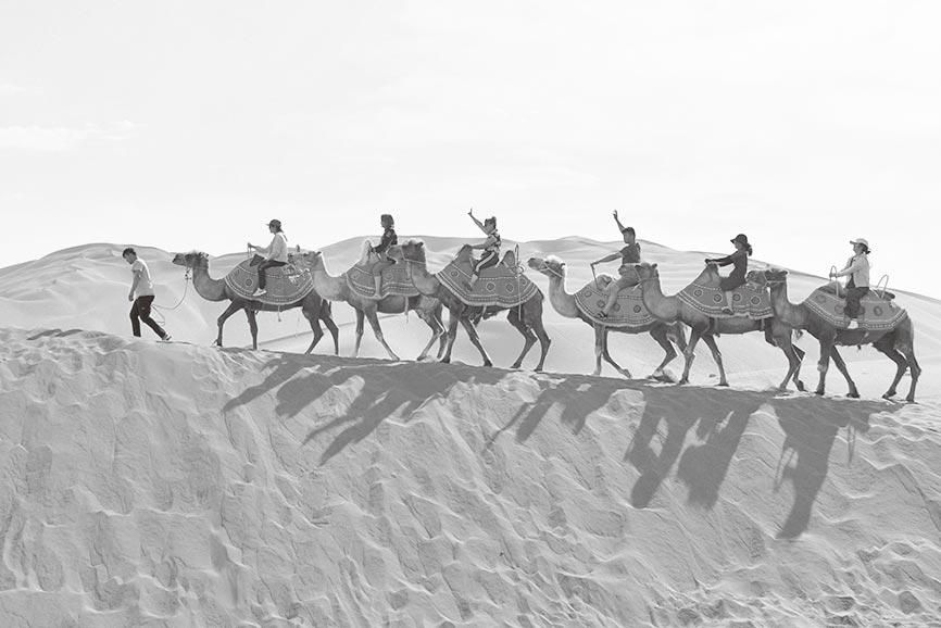 遊客在新疆庫木塔格沙漠風景區騎駱駝。(新華社資料照片)