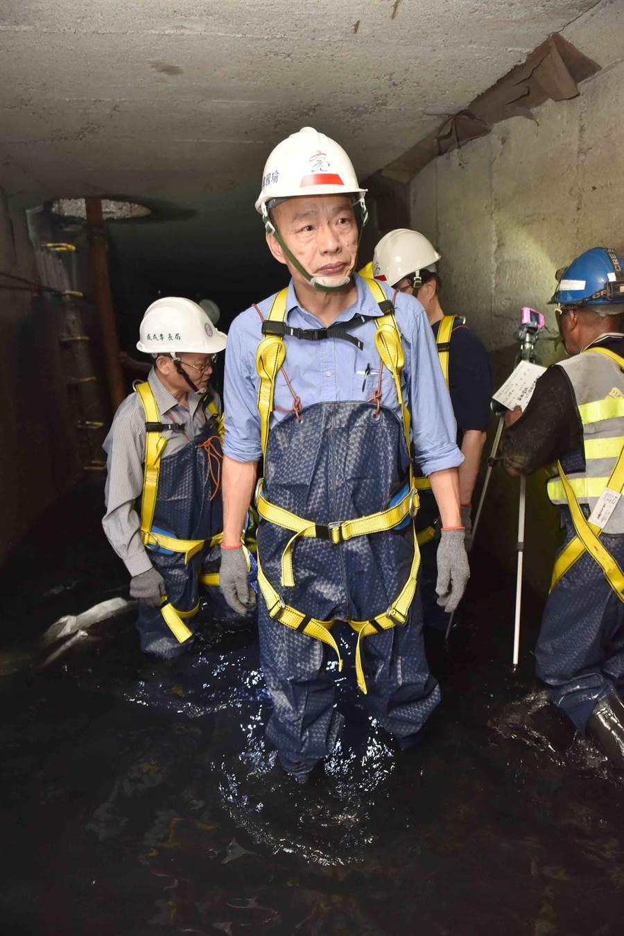 高雄巿長韓國瑜日前穿青蛙裝進入三民區同盟二路與自立一路口視察下水道。(曹明正翻攝)