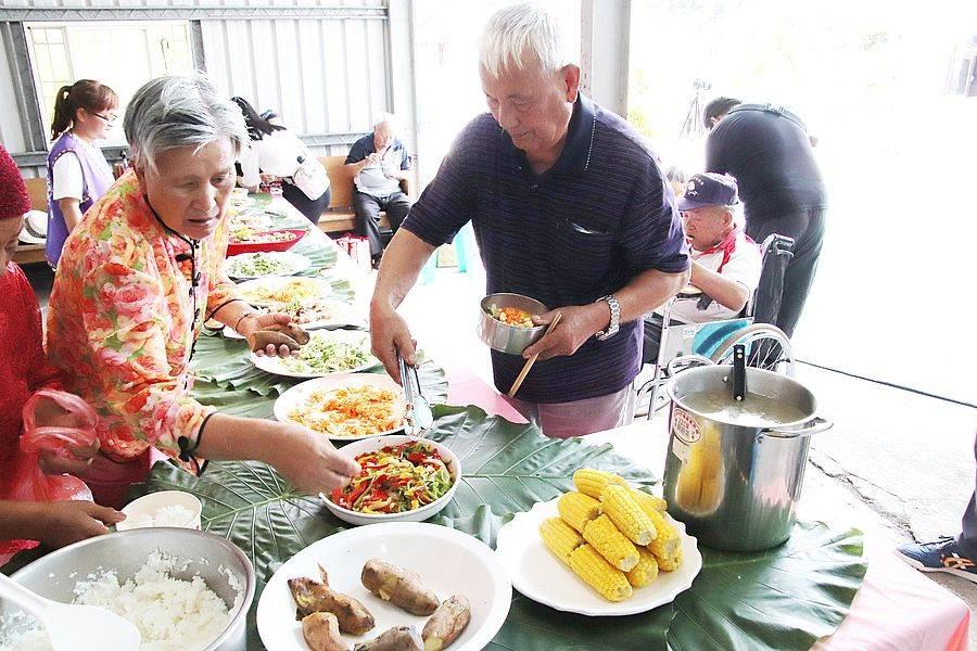 新武部落長輩們自備環保餐具,採自助的方式開心排隊取餐。余阿公(右)表示:「大家聚在一起吃很滿足,不再無聊了!」。(圖取自活動官網)