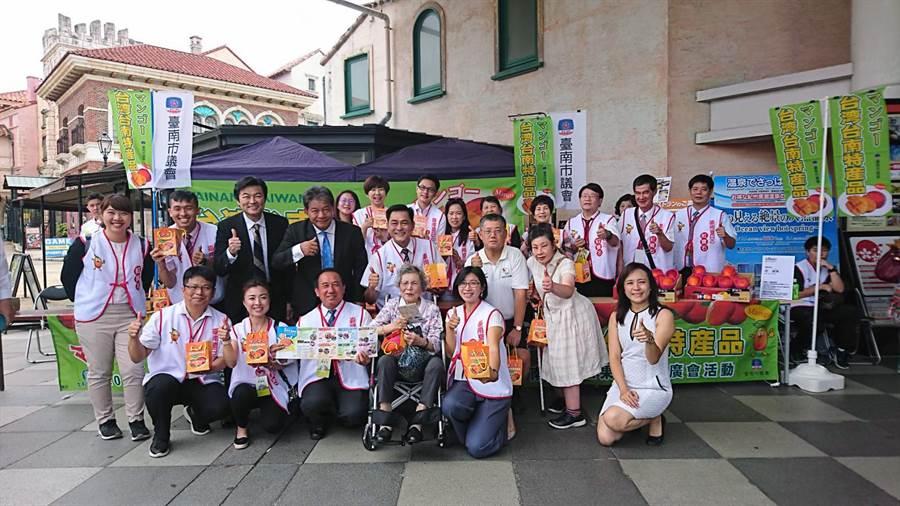 台南市議會在日本和歌山市著名的黑潮市場舉行台南芒果推廣會,80多歲的阿嬤(前排左四)也坐著輪椅前來排隊拿芒果。(南市議會提供)