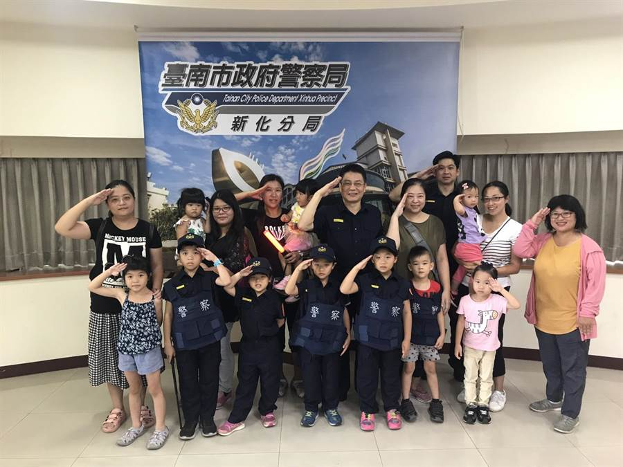 高雄親子團訪新化分局,小小孩開心試穿新式警察制服。(劉秀芬翻攝)