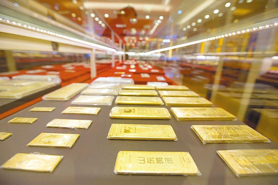 寬鬆貨幣政策將支撐黃金投資的需求,圖為山西太原金店工作人員清點金條。(中新社)