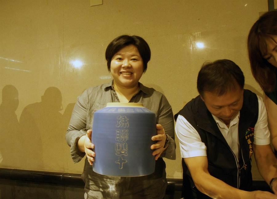 台中市議會副議長顏莉敏將倒入茶葉的茶倉捧起,相約10年後再一起共飲。(王文吉攝)