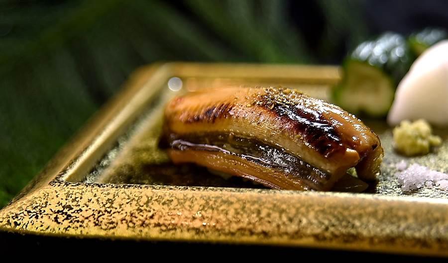 〈初刀料亭.晶華〉的〈星鰻握壽司〉,星鰻來自東京灣,廚師先滷煮再炙烤後再涮上用以醬油和味醂調製的醬汁提味。(圖/姚舜)