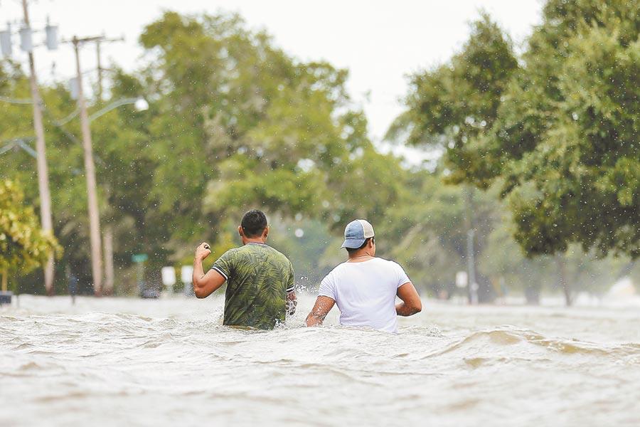 熱帶風暴巴瑞侵襲路易斯安那州,最大城市紐奧良遭受重創。沿海城市曼德維爾大淹水,民眾13日在淹水高度及腰的街道艱難前進。(路透)