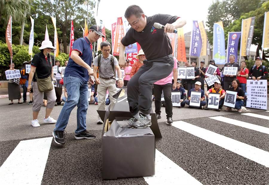 聯合會成員踩破黑色紙箱,抗議官方的薪資審議是黑箱作業。(范揚光攝)