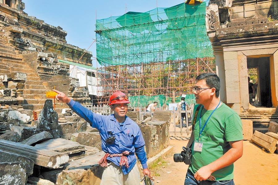 2014年2月1日,中國工程師(右)在吳哥古跡與柬埔寨工人交流修復工作內容。(新華社)