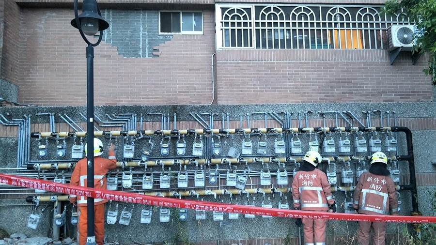 新竹市明湖路1處社區大樓外牆磚面剝落,造成1樓8具瓦斯表被擊毀,消防員到場拉起封鎖線。(徐養齡翻攝)