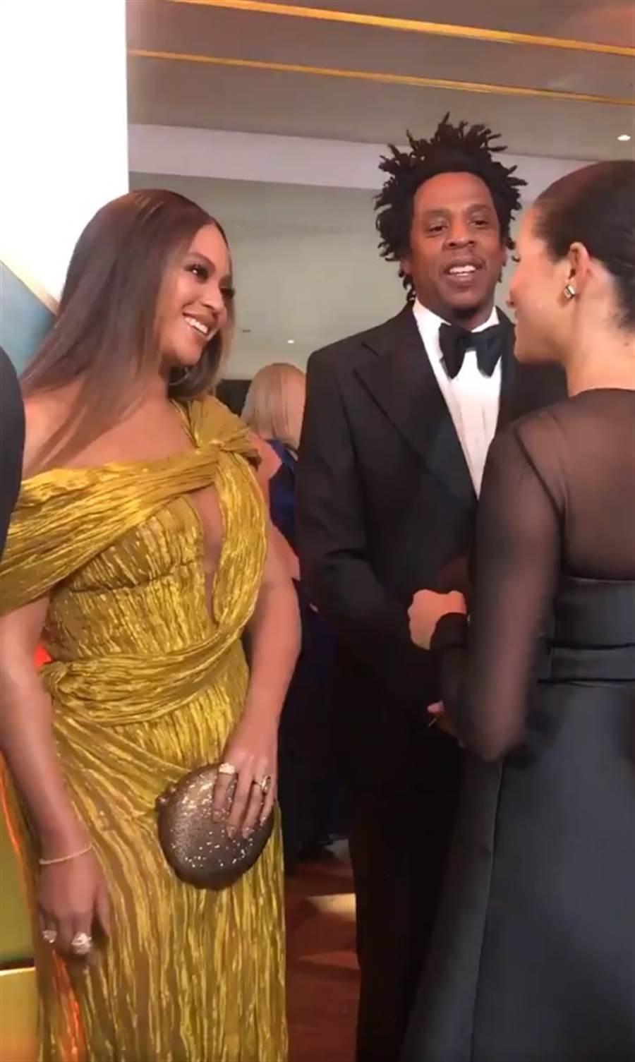 碧昂絲(Beyoncé)與梅根、哈利王子見面時,一直用手拿包檔住高衩部分,以示對哈利夫婦的尊重。(圖/Twitter @BeyLegion)