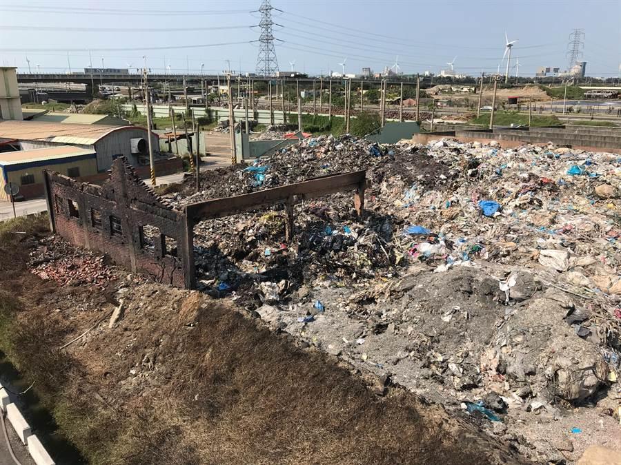 線西鄉中華路私人回收場大火過後,廢棄塑膠和火灰等廢物還推積如山,被質疑農業用地竟可以推放廢棄物?違反地目使用。(吳敏菁翻攝)