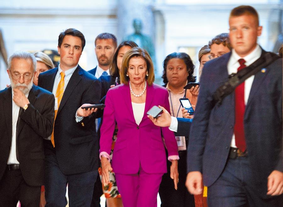 民主黨籍眾議院議長裴洛西(中)再槓上川普!她雖與黨內「四人幫」不和,但當川普與她們開罵,她仍在眾院呼籲譴責川普種族歧視的言論。(法新社)