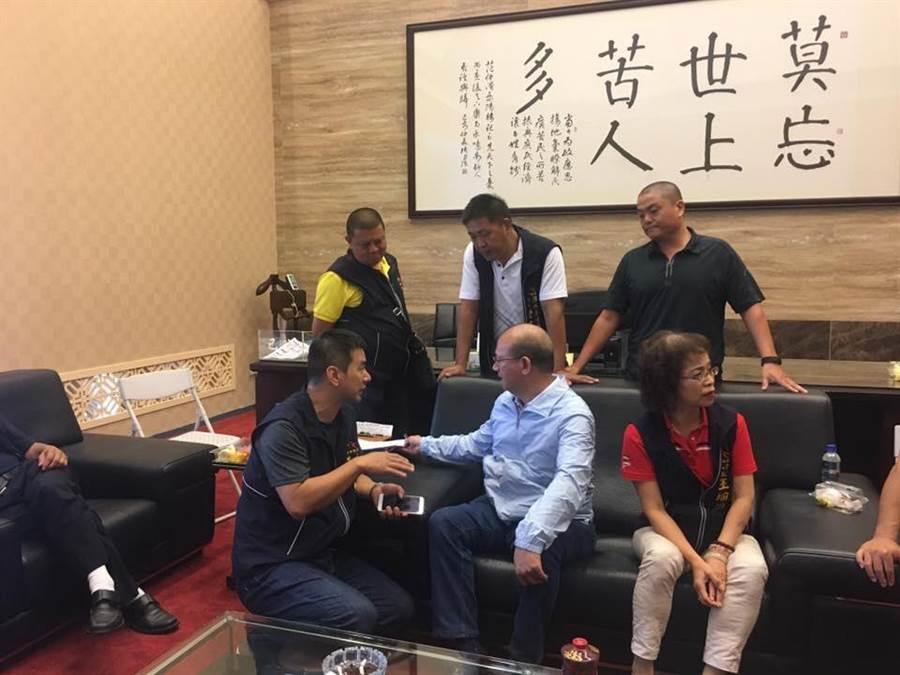 台中市议长张清照(中)办公室挂着高雄市长韩国瑜常说的「莫忘世上苦人多」,以庶民为重,民意优先,铭记在心。(图/摘自张清照脸书)