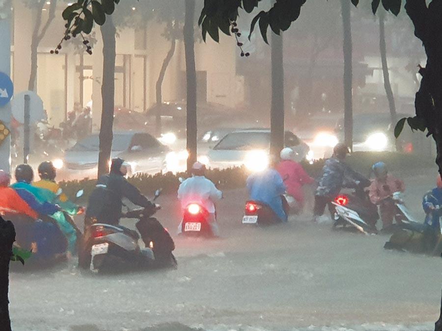 高雄市區19日下午受旺盛西南氣流影響降下豪雨,市府四維行政中心周邊道路因嚴重積水、水深及膝,交通幾乎癱瘓。(袁庭堯攝)