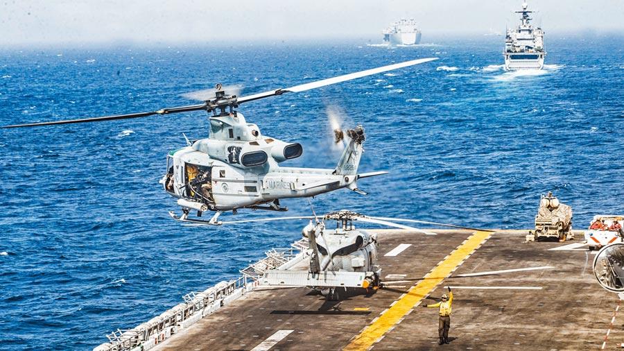 一架美軍陸戰隊UH-1Y毒液(UH-1Y Venom)直升機18日正從兩棲攻擊艦「拳師號」起飛。美方宣稱,「拳師號」當天在荷姆茲海峽摧毀了1架伊朗無人機,美媒稱摧毀無人機的武器,是最新式電子戰武器「輕型海上防空綜合系統」(LMADIS,甲板右上方)。(路透)