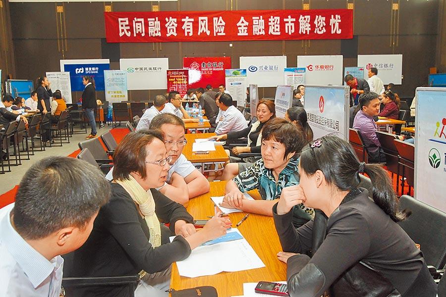 江蘇南通市企業經營者與擔保公司工作人員在「金融超市」現場交流。(新華社資料照片)