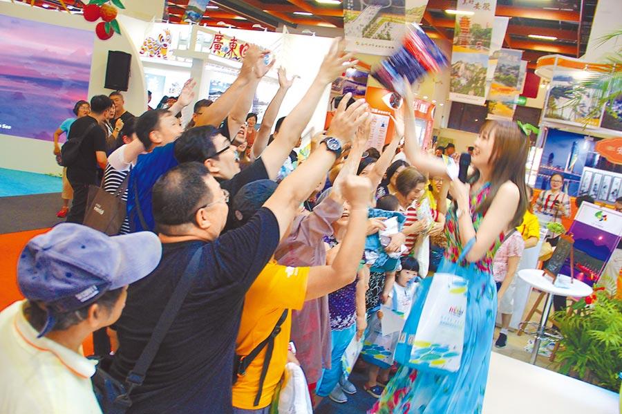 2019海峽兩岸台北夏季旅展19日登場,大陸多省市展攤都有有獎徵答,民眾搶拿小禮物。(記者李鋅銅攝)