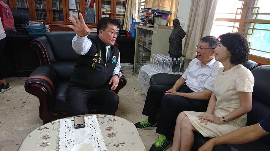 台北市長柯文哲(白襯身者)與夫人陳佩琪聽起聖母廟主委王明義說明廟史感到很有意思。(程炳璋攝)