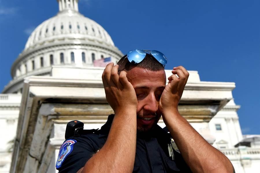 致命熱浪周末席捲美國東岸,多個大城體感溫度飆破攝氏40度。圖為一名警察在華府國會大廈前熱到不斷擦汗的模樣。(圖/美聯社)