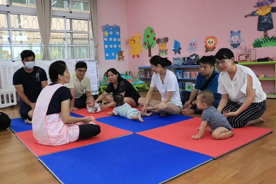 東區公共托育中心21日開幕,家長一起在教室裡練習為嬰兒按摩,促進親子關係。(張亦惠攝)