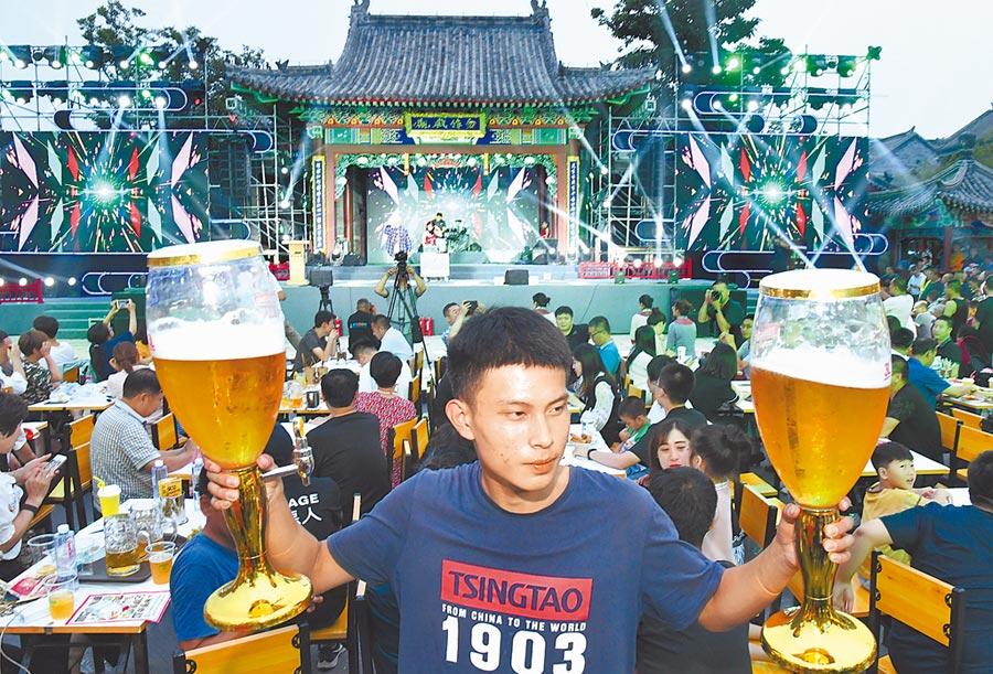 7月12日,一名男士在青島國際啤酒節舉起啤酒杯慶祝。(新華社)