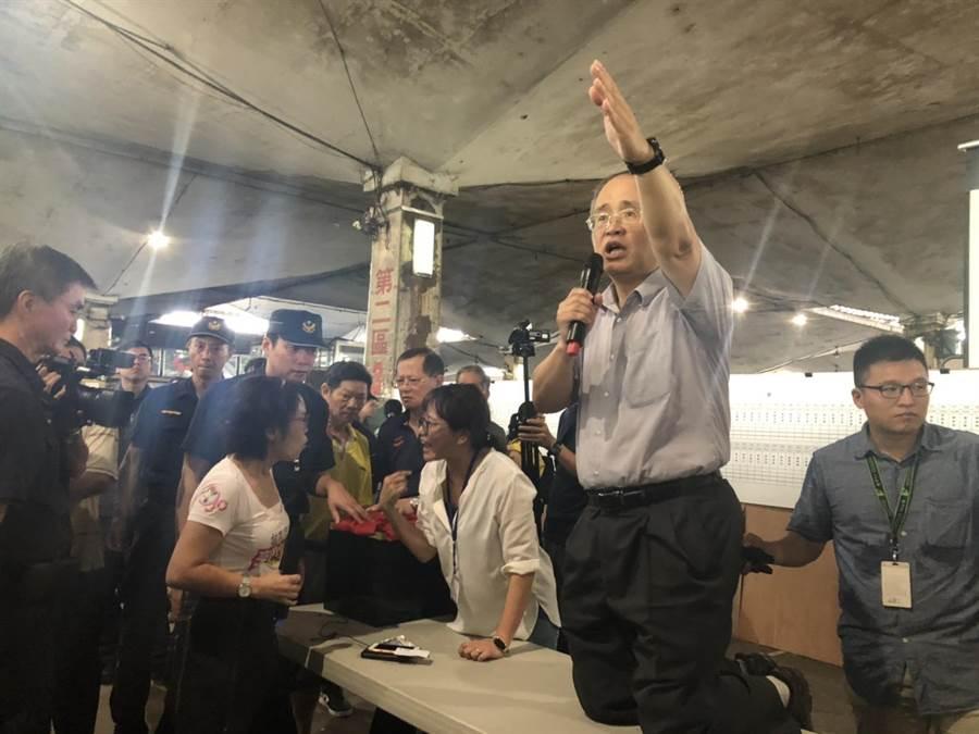 主持會議的北市參議王夢龍以跪姿與攤商隔空交火。(吳堂靖攝)