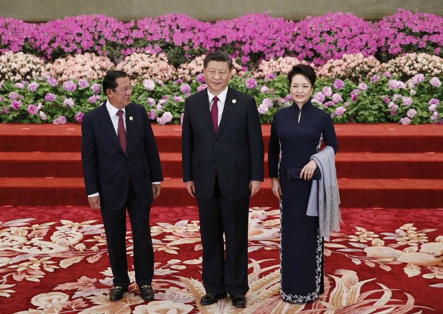 柬埔寨總理洪森(左)今年4月參加北京「一帶一路」會議時,由中共國家主席習近平與其夫人在人民大會堂接見。(圖/美聯社)