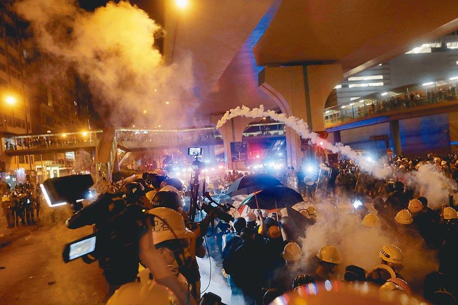 反送中示威者包圍中聯辦,以雞蛋、黑漆攻擊中聯辦招牌及大陸國徽,港警預告清場,雙方晚間10點在信德中心衝突,警方多次施放催淚彈,現場煙霧瀰漫。(法新社)
