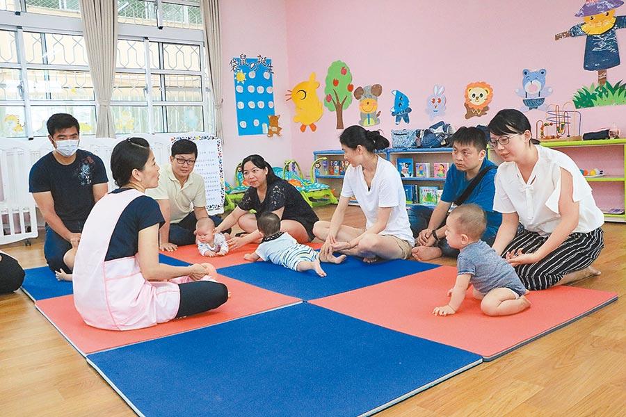 東區公共托嬰中心21日開幕,家長一起在教室裡練習為嬰兒按摩,促進親子關係。(張亦惠攝)