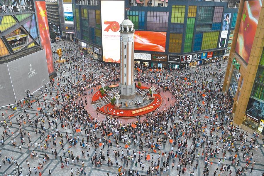 7月19日,「禮讚新中國.奮進新時代」慶祝中共建政70周年主題快閃活動在重慶解放碑舉行,現場演奏交響樂,民眾一同唱響《我和我的祖國》。(中新社)