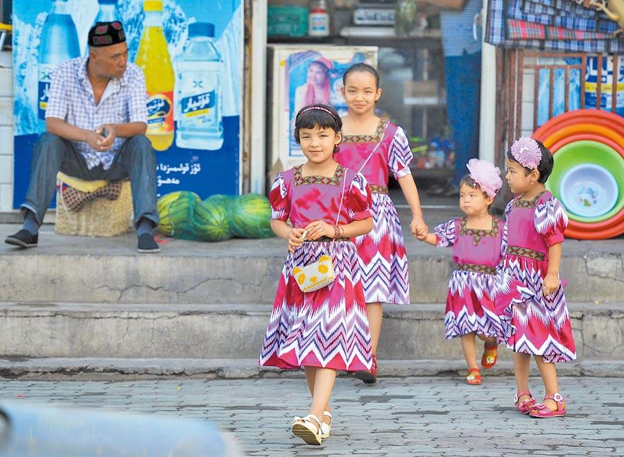 2016年7月6日,伊斯蘭教傳統節日——開齋節,維吾爾族小朋友身著色彩華麗的節日服裝外出玩耍。(中新社)