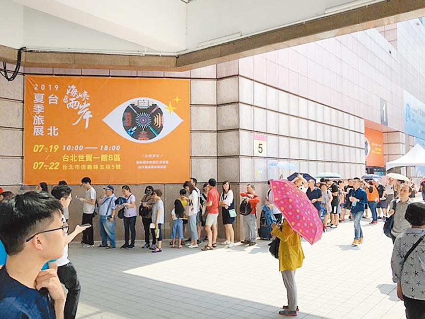兩岸旅展逢周日,逛展民眾在大門外大排長龍。(記者李鋅銅攝)