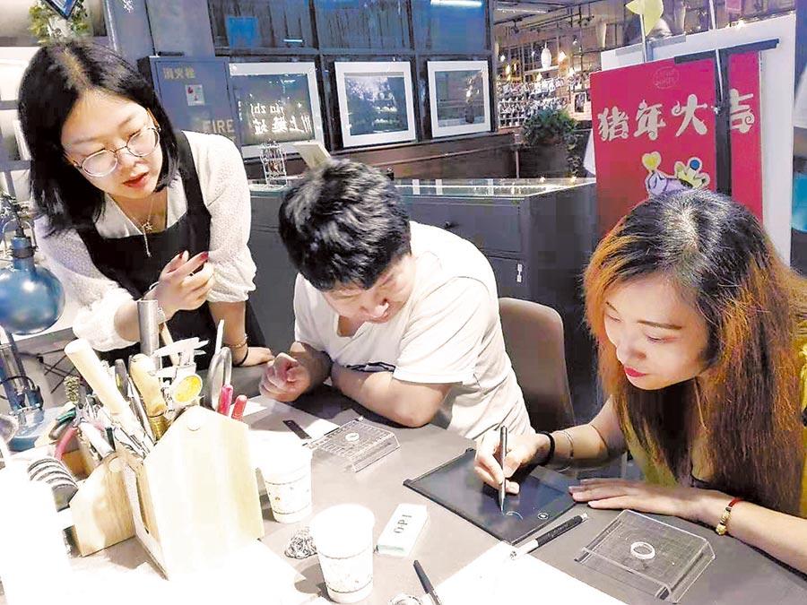 婁露(左1)在指導顧客手工製作銀飾品。(李倩文攝)