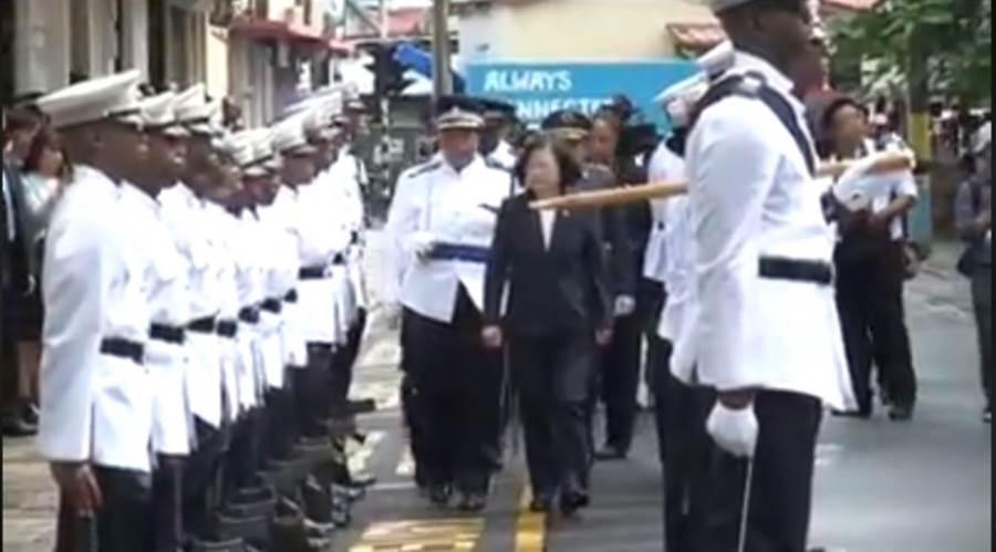 蔡英文总统(中前)出访友邦圣露西亚,穿深色西装裤装阅兵。(翻摄网友脸书影片)