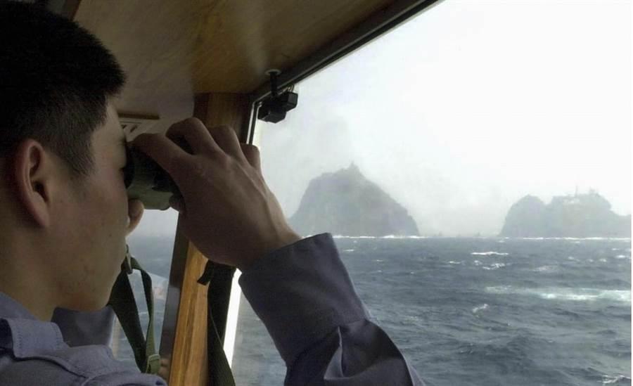 韓國海岸防衛隊以望遠鏡眺望獨島(日本稱竹島)的資料照。(美聯社)
