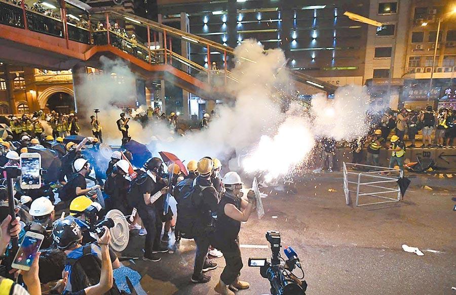 7月21日晚十時許,集結上環的示威者衝擊警方防線,警方投放催淚彈。(中新社)