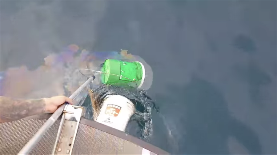 潛水教練王銘祥發現象鼻岩外海,有23桶船隻機油在海中汙染環境,趕緊打撈上船。(王銘祥提供)