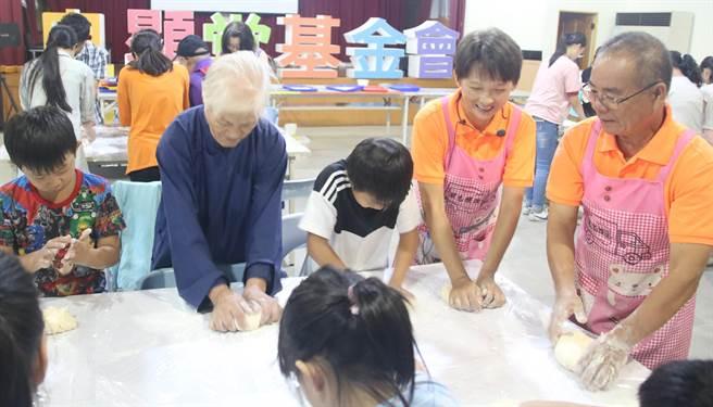 ▲饅頭夫妻林波、靳寶儀傳愛到良顯堂,與陳綢阿嬤教導小朋友如何揉麵團。(楊樹煌攝)